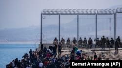 Bevándorlók várnak, hogy bejuthassanak a Marokkó és Spanyolország határához közeli Ceuta spanyol enklávéba, 2021. május 18-án.