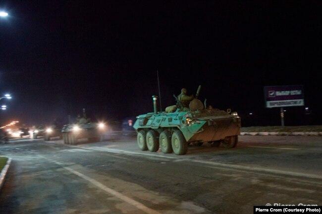 Симферополь, 28 февраля 2014. Российская военная колонна проезжает плакат с рекламой референдума