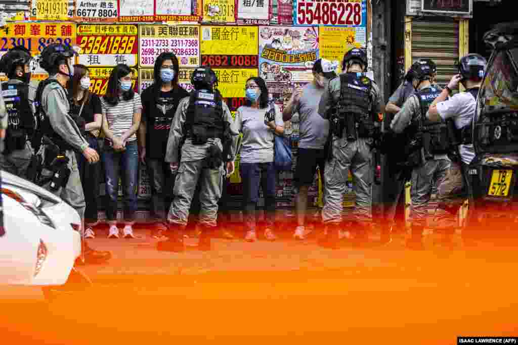 Police stop and search people (C) during a protest against China's planned national security law in Hong Kong on June 28, 2020.