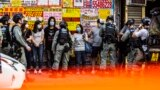 CHINA -- HONG KONG -- Police stop and search people (C) during a protest against China's planned national security law in Hong Kong on June 28, 2020.