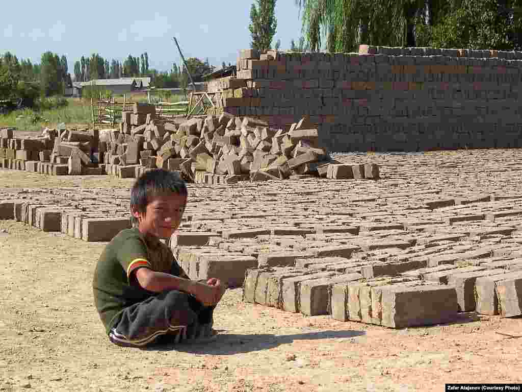 A Kyrgyz child takes a break from making clay bricks to sell.