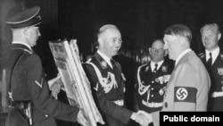 Гиммлер нацистердің жетекшісі Адольф Гитлерге сыйлық тапсырып тұр. Сәуір айы 1939 ж.