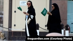 Səudiyyəli qadınlar əllərində ölkə bayrağı tutublar