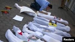 Мужчина прикрепляет надпись к символическим трупам жертв предполагаемой химической атаки в Сирии на акции протеста у здания ООН. Нью-Йорк, 21 августа 2013 года.