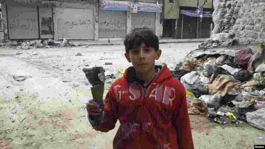 A boy holds mortar shrapnel in a handout picture taken by a Syrian National Council member in Karm Al Zaytoon, a neighborhood of Homs, on February 23. (REUTERS/Moulhem Al-Jundi/Handout)
