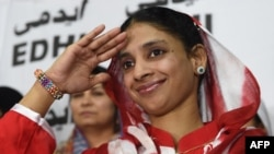 Deaf-mute Indian woman Geeta salutes the media before leaving for the airport from the EDHI Foundation in Karachi on October 26, 2015