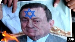 Protesters in Jordan set a picture of Egyptian President Hosni Mubarak on fire as they demonstrate against the Israeli offensive in Gaza outside the Egyptian Embassy in Amman. The protesters also want Egypt to open the Rafah border crossing with Gaza.
