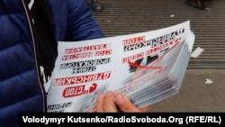 Чоловік роздає листівки з агітацією проти кандидата Олександра Дубінського