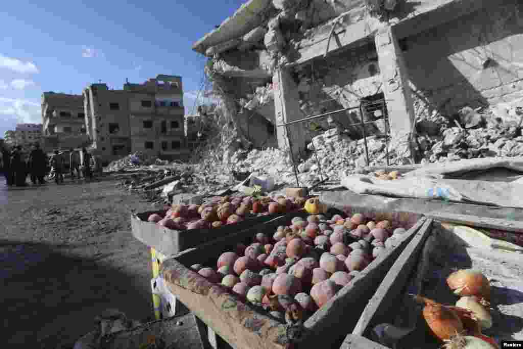 Vegetables are covered in dust as people inspect a site hit by what activists said were air strikes carried out by the Russian Air Force on a busy market in the town of Ariha, in Idlib Province, Syria. (Reuters/Ammar Abdullah)