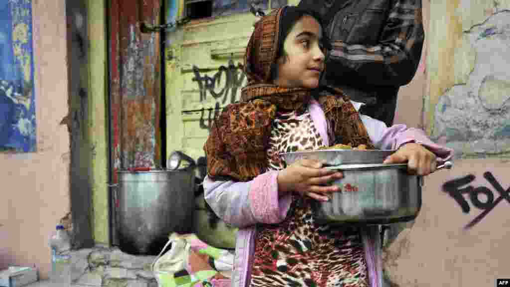 Fatima, an Afghan immigrant, carries food donated by activists from a soup kitchen in a poor neighborhood in Athens, Greece.