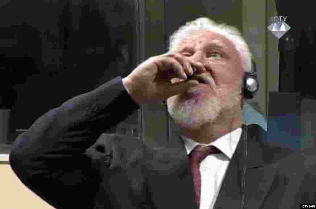 "Convicted war criminal Slobodan Praljak brings a bottle to his lips at the International Criminal Tribunal for the former Yugoslavia in The Hague on November 29. Praljak yelled, ""I am not a war criminal!"" and drank a poisonous substance, seconds after judges reconfirmed his 20-year prison sentence. He died a short time later. (ICTY via AP)"