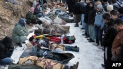 Locals gather in front of the bodies of people who were killed in an air strike in southeastern Turkey on December 29.