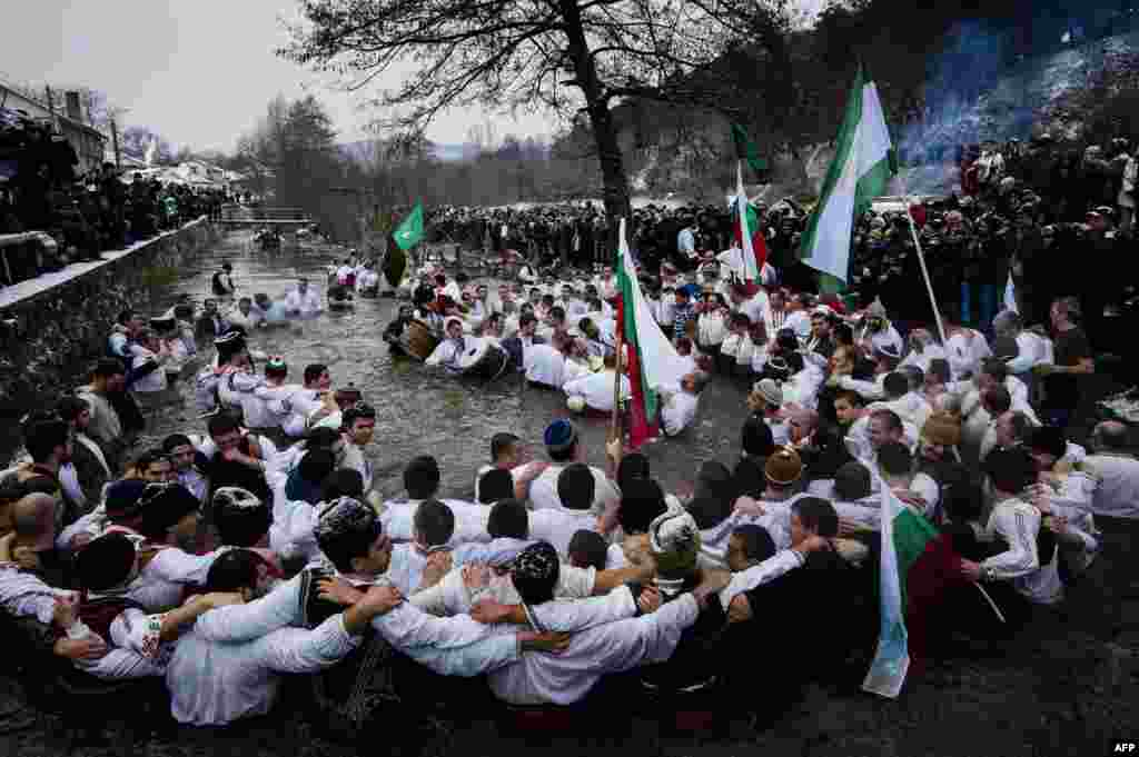 Men dance in the icy winter waters of the Tundzha River in the Bulgarian town of Kalofer as part of Epiphany Day celebrations. As a tradition, an Eastern Orthodox priest throws a cross in the river and it is believed that the one who retrieves it will be healthy through the year, as well as all those who dance in the icy waters. (AFP/Dimitar Dilkoff)