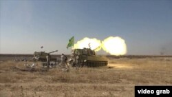 Iraqi Army self-propelled 155mm Paladin howitzer artillery fires from the east of Mosul at IS militants.