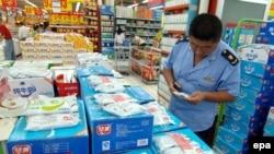 Судебный исполнитель местной администрации проверяет молочные продукты в супермаркете города Циндао. 19 сентября 2008 года