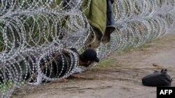 Біженець протискається через паркан з колючого дроту на кордоні Угорщини і Сербії, 26 серпня 2015 року