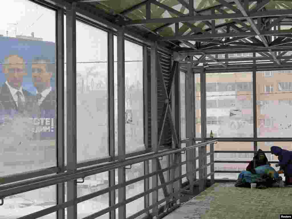 Homeless people shelter in a covered walkway near an election poster for the United Russia party in the city of Kazan, in the Tatarstan Republic, on November 30. (REUTERS/Anton Golubev)