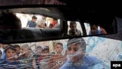 По мнению наблюдателей, Палестина все более явно скатывается к гражданской войне. Дети у уничтоженной в ходе стокновений машины ХАМАС.