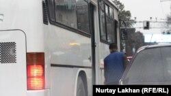 Алматыда қала ішінде жолаушы таситын автобус жанында тұрған адам. (Көрнекі сурет)
