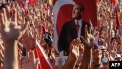 Демонстранты, осуждающие попытку переворота, стоят с поднятыми руками на площади Таксим в Стамбуле. На плакате - фото основателя современной Турции Мустафы Кемаля Ататюрка. 24 июля 2016 года.