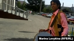 Индийский музыкант из Дели созывает покупателей на ярмарку. Семей, 29 июня 2012 года.