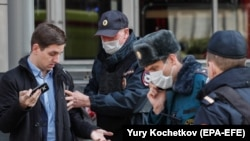 Moscow police officers stop a man for allegedly breaking self-isolation rules amid a coronavirus lockdown on April 9.