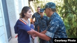 One of several undated photos of Gulnara Karimova -- apparently under house arrest and being restrained by security troops -- released in September by Ryan Locksley.