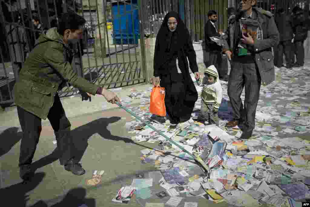 An Iranian man sweeps electoral leaflets for Iran's upcoming parliamentary elections after Friday Prayers outside Tehran University on February 24.