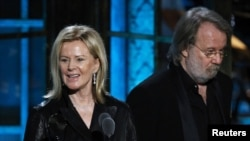 Two ABBA members, Anni-Frid Lyngstad and Benny Andersson, celebrate their induction into the Rock and Roll Hall of Fame.