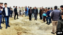 Iraqi Kurds inspect a crater reportedly caused by an Iranian missile initially fired at Iraqi bases housing U.S. and other U.S.-led coalition troops, in the Iraqi Kurdish town of Bardarash in the Dohuk governorate, January 8, 2019