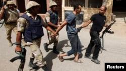 عناصر من الأمن المصري تقتاد مشتبهاً به في كرداسة