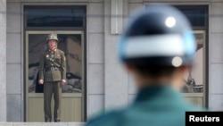 Солдат армии КНДР (слева) и южнокорейский солдат несут службу по охране границы у разделительной линии между двумя странами