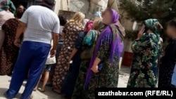 Жители одного из столичных микрорайонов стоят в очереди за продуктами перед задним входом государственного магазина