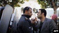 Demonstrant se raspravlja sa policajcem tijekom prosvjeda u centru Tunisa, 17. siječanj 2011.