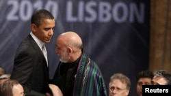U.S. President Barack Obama (left) greets his Afghan counterpart, Hamid Karzai, before the opening session of the second day of the NATO Summit in Lisbon on November 20.