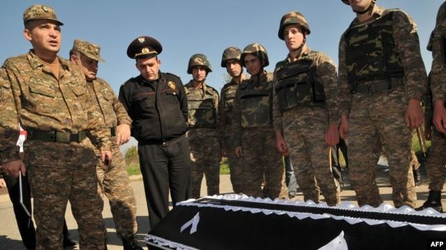 Armenia -- Servicemen stand near the coffin of Manvel Saribekyan, an Armenian taken captive by Azerbaijani forces, during his body's return to Azerbaijan on the Ijevan-Qazax highway near the village of Kayan, 04Nov2010