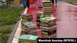 Көшеде жауын астында қалған кітаптар. (Көрнекі сурет.)
