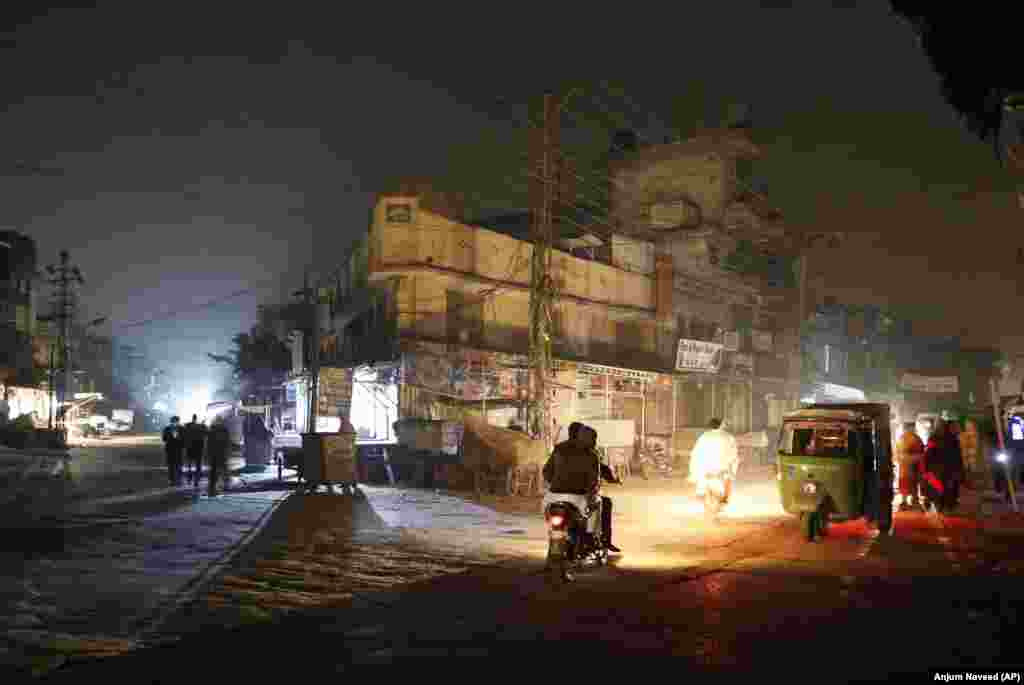 People are silhouetted against vehicle headlights on a dark street during widespread power outages in Rawalpindi, Pakistan. Pakistan's national power grid experienced a major breakdown, leaving millions of people in darkness. (AP/Anjum Naveed)