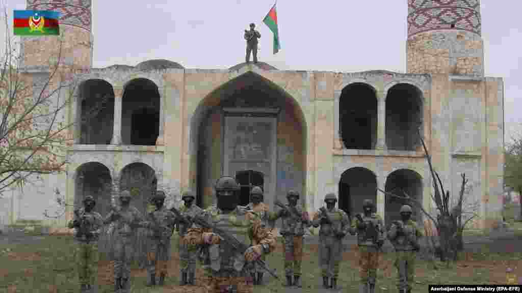"Azerbaijani servicemen pose in front of the Agdam mosque in a propaganda video after the town returned to Azerbaijani control on November 20. Lohr says he is ""curious how it will look now"" and wonders ""what the Azerbaijanis will do with [Agdam]."" Thousands of displaced Azerbaijanis have vowed to return and rebuild it."
