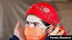 Az UNICEF egy munkatársa segít egy belföldi menekültnek Afganisztánban felvenni a maszkot egy rögtönzött táborban a koronavírus idején. Dzsalálábád, 2020. június 22.