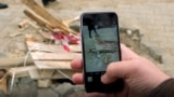 Kosovo: Dren Shahini takes a photo of damages in one road in Prishtina.
