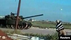 Үкімет әскері танкіне жарылғыш лақтырып тұрған адам. Дераа, 25 сәуір 2011 жыл. (Көрнекі сурет)