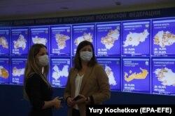 دو زن که ماسک بر چهره دارند مقابل نمایشگرهای نتایج منطقهای انتخابات در کمیسیون مرکزی انتخابات روسیه