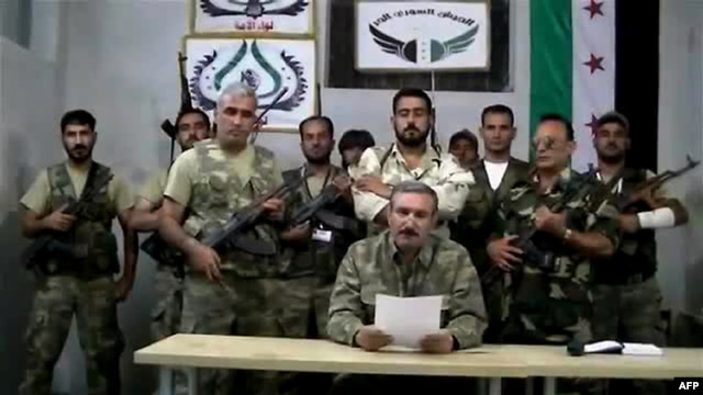 Free Syrian Army chief Riad al-Asaad (center) reading a statement from an undisclosed location in Syria in September 2012. (screen shot)