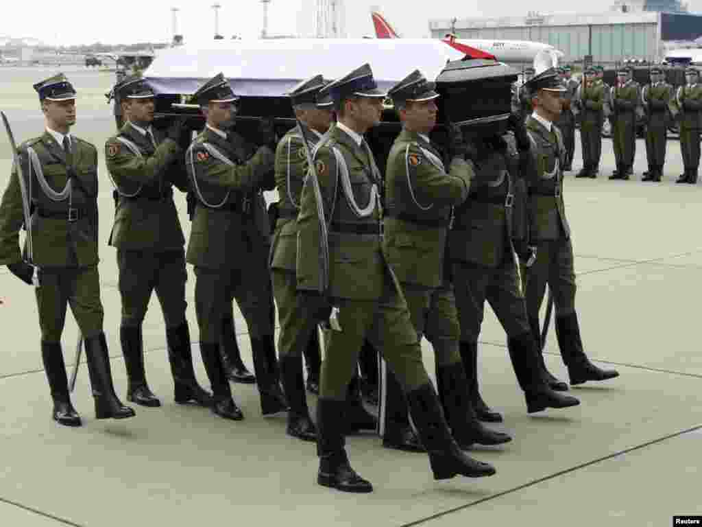 Soldiers carry President Kaczynski's coffin as it arrives at the airport in Warsaw.