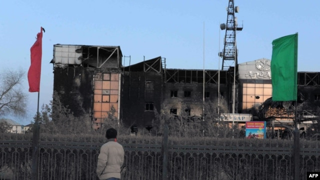 A man stands in front of burned-out official buildings in Zhanaozen on December 18.
