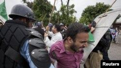 Мұсылмандар туралы фильмге наразылық білдіріп АҚШ елшілігіне келгендер полицияның тосқауылына кезікті. Исламабад, Пәкістан, 14 қыркүйек 2012 ж.