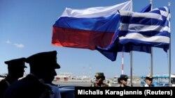 Сотрудники полиции и военные на фоне флагов Греции, России и Европейского союза. Иллюстративное фото.