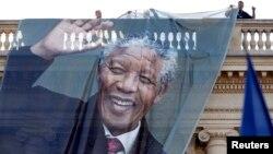 Жұмысшылар ОАР-дың бұрынғы президенті Нельсон Манделаның суретін салынған баннерді іліп жатыр. Париж, 6 желтоқсан 2013 жыл.