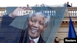 Рабочие устанавливают баннер с изображением покойного экс-президента ЮАР Нельсона Манделы.